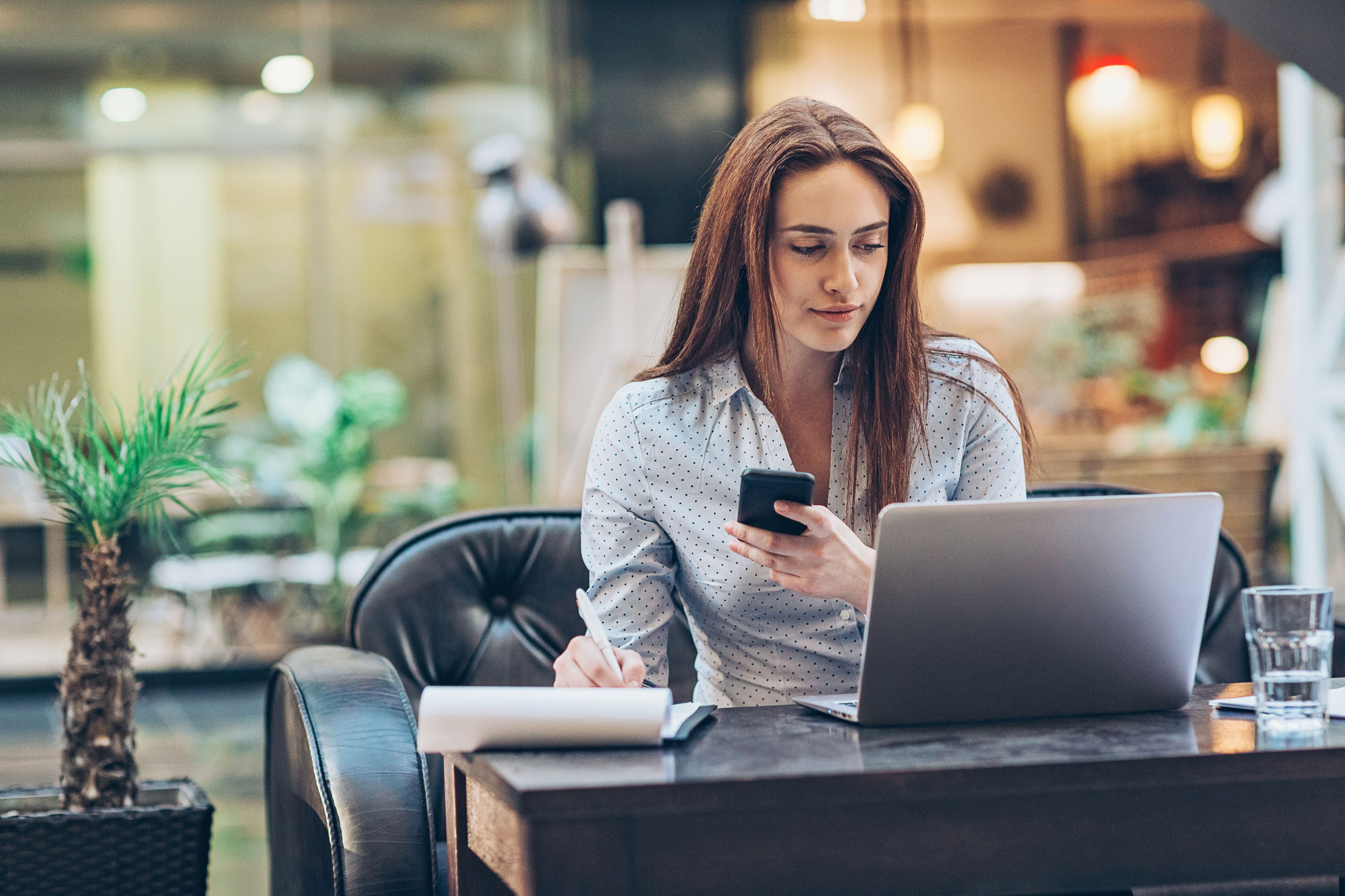 woman working with laptop, phone and notepad - The Link App
